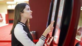 Boleto de compra de la película del adolescente de la máquina expendedora en el cine La hembra hace gestos por la pantalla táctil almacen de metraje de vídeo