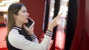 Boleto de compra de la película del adolescente de la máquina expendedora en el cine Mujer que usa hablar móvil con el amigo almacen de video