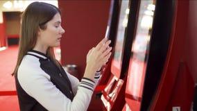 Boleto de compra de la película del adolescente de la máquina expendedora en el cine El usar de la mujer móvil, haciendo las foto almacen de metraje de vídeo