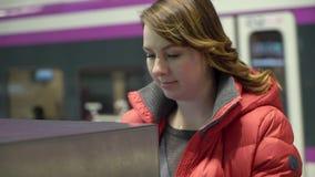 Boleto de la compra de la muchacha en terminal o la atmósfera con en el ferrocarril almacen de metraje de vídeo