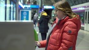 Boleto de la compra de la muchacha en terminal o la atm?sfera con en el ferrocarril almacen de metraje de vídeo