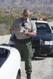 Boleto de la escritura del poli de tráfico Fotografía de archivo libre de regalías