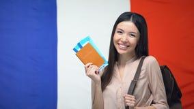 Boletos asiáticos felices del pasaporte y del vuelo de la tenencia de la mujer contra la bandera francesa, viaje almacen de metraje de vídeo
