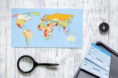 Boletos de la búsqueda y de la compra para el viaje Boletos y mapa del mundo en la opinión superior del fondo de madera ligero de Foto de archivo