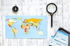 Boletos de la búsqueda y de la compra para el viaje Boletos y mapa del mundo en la opinión superior del fondo de madera ligero de Fotografía de archivo