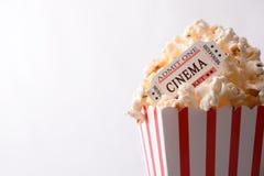 Boletos de las palomitas y de la película en la opinión superior del fondo blanco Foto de archivo libre de regalías