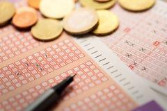 Boletos de lotería con las monedas y la pluma Fotografía de archivo libre de regalías