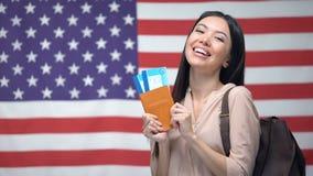 Boletos emocionados del pasaporte y del vuelo de la tenencia de la mujer contra fondo de la bandera de los E.E.U.U. almacen de metraje de vídeo