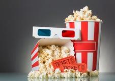Boletos, palomitas y vidrios 3D de la película en un gris Fotos de archivo libres de regalías