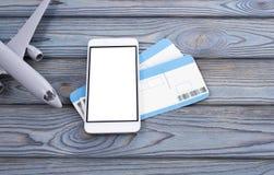 Boletos para el avión, smartphone con una pantalla blanca Fotos de archivo libres de regalías