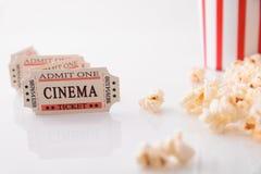 Boletos y palomitas de la película en el primer blanco de la vista delantera de la tabla Imagen de archivo