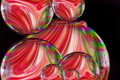 Bolha de sabão com as pinturas líquidas coloridas misturadas junto criando o teste padrão cores do arco-íris no fundo preto ilustração do vetor
