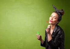 Bolha de sabão de sopro da mulher bonita no fundo do copyspace Imagens de Stock