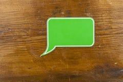 bolha plástica verde do discurso no fundo de madeira imagem de stock