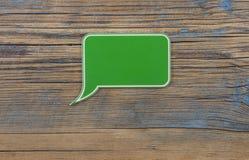 bolha plástica verde do discurso no fundo de madeira fotos de stock