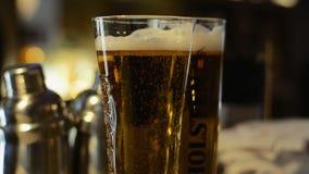 Bolhas da cerveja do close-up no vidro filme