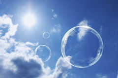 Bolhas de sabão de flutuação contra o céu azul e nuvens ensolarados claros Imagens de Stock