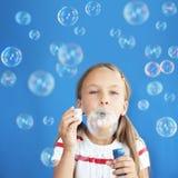 Bolhas de sabão de sopro da criança fotos de stock royalty free