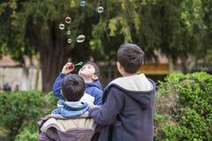 Bolhas de sabão de sopro da criança fora Imagens de Stock Royalty Free