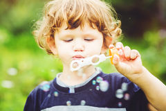 Bolhas de sabão de sopro da criança, retrato do close up foto de stock royalty free