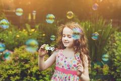 Bolhas de sabão de sopro da menina encaracolado foto de stock