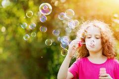 Bolhas de sabão de sopro da menina no parque do verão Fundo a imagens de stock