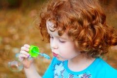 Bolhas de sabão de sopro da menina, retrato do close up bonito Foto de Stock Royalty Free