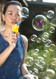 Bolhas de sabão de sopro da mulher nova imagens de stock royalty free