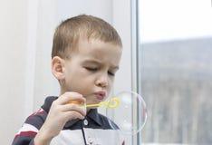 Bolhas de sabão de sopro do menino. Imagens de Stock Royalty Free