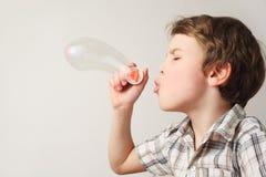 Bolhas de sabão de sopro do menino no fundo branco imagem de stock royalty free
