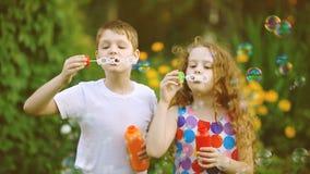 Bolhas de sabão de sopro felizes do menino e da menina no parque do verão filme