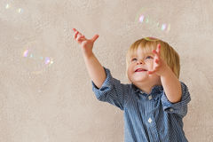 Bolhas de sabão de travamento da criança positiva Fotografia de Stock