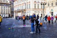 Bolhas de sabão de voo dos povos que formam a praça da cidade velha Praga, República Checa Fotos de Stock Royalty Free