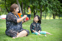 Bolhas de sabão iblowing asiáticas felizes da mãe e da filha imagens de stock
