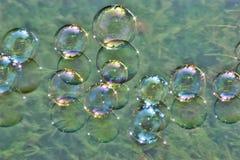 Bolhas de sabão na água fotos de stock