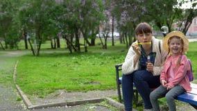 Bolhas de sabão de sopro da família feliz no parque de lilás de florescência no dia de mola ensolarado filme