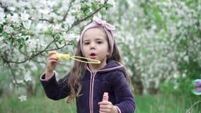 Bolhas de sab?o de sopro da menina feliz no jardim da mola Movimento lento filme