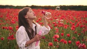 Bolhas de sabão de sopro da menina no campo de florescência de papoilas vermelhas no por do sol, movimento lento filme
