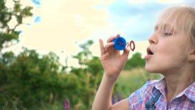Bolhas de sabão de sopro da menina no gramado verde vídeos de arquivo