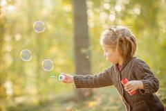 Bolhas de sabão de sopro da menina no parque do outono Fundo que tonifica para o filtro do instagram A criança tem o divertimento foto de stock royalty free