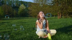 Bolhas de sabão de sopro da menina no parque da mola Movimento lento vídeos de arquivo