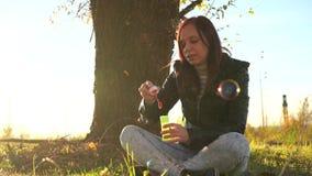 Bolhas de sabão de sopro da mulher exteriores Menina adolescente que tem o divertimento no parque - bolhas de sabão de sopro video estoque