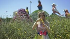 Bolhas de sabão de sopro da mulher loura nova 'sexy' no jardim Consideravelmente sonhar a menina bonito no vestido engraçado do l filme