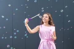 Bolhas de sabão de sopro do adolescente contra a parede cinzenta imagem de stock royalty free