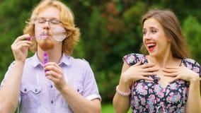 Bolhas de sabão de sopro dos pares, tendo o divertimento fotos de stock royalty free