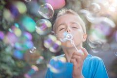 Bolhas de sabão de sopro no sol do verão imagem de stock royalty free