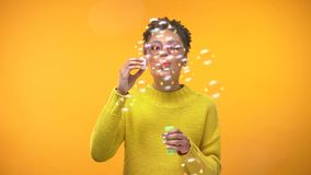 Bolhas de sab?o de sopro da mulher negra alegre no fundo amarelo, felicidade da juventude fotos de stock