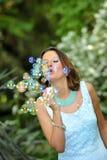 Bolhas de sabão de sopro novas da menina bonita e feliz ao ar no fundo natural do parque verde no conceito do encanto Imagens de Stock