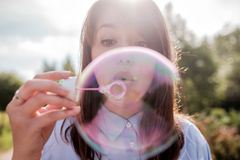 Bolhas de sopro da menina ao ar livre Foco nos bordos Fotografia de Stock