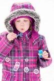 Bolhas de sopro da menina na neve imagem de stock royalty free